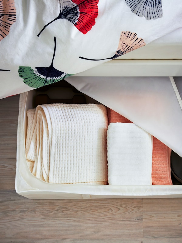 Towels stored in a white SKUBB storage case under a NESTTUN bed with a TOVSIPPA quilt cover with a floral pattern.