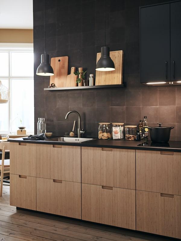 Dans cette cuisine de style contemporain, les façades en bambou voisinent avec des murs carrelés de noir et des accessoires noirs également.