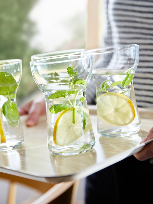 Four OMTÄNKSAM glasses on a leaning FÖRMEDLA tray. The anti-slip surface helps the glasses to stay steady.