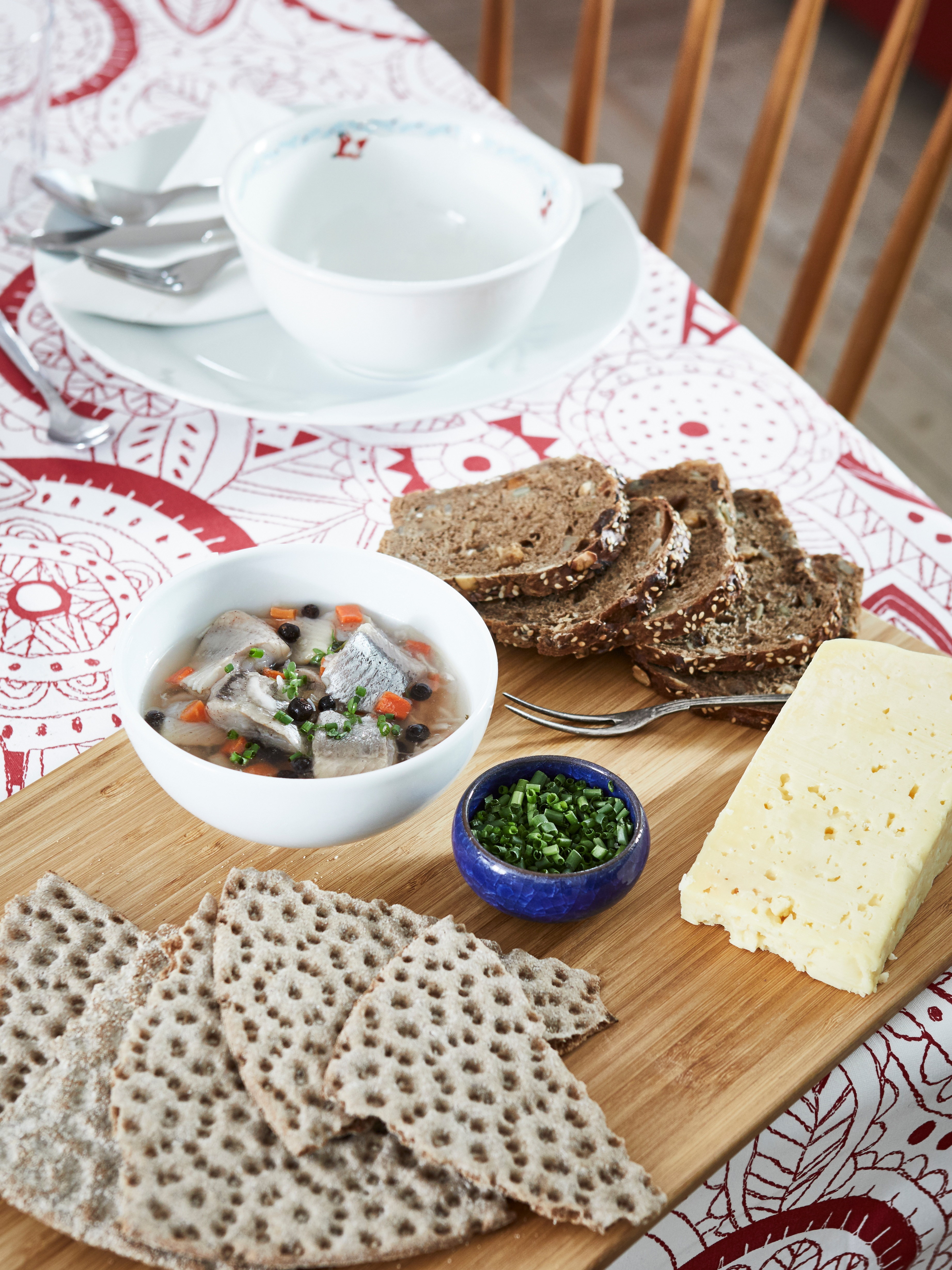 White bowl with SILL INLAGD marinated herring with onions and carrots, on a wooden board with bread, cheese and other foods.