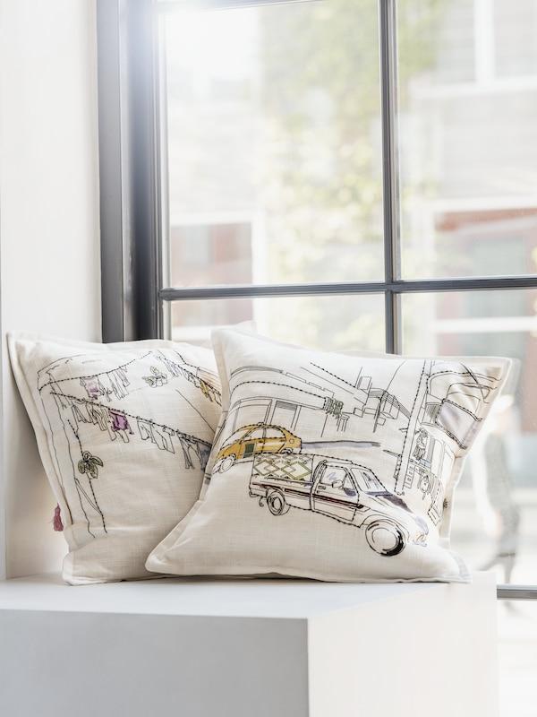 アンマンの洗濯物を干したロープと車が手刺繍で描かれたクッション2個が、窓の前に置いてある。