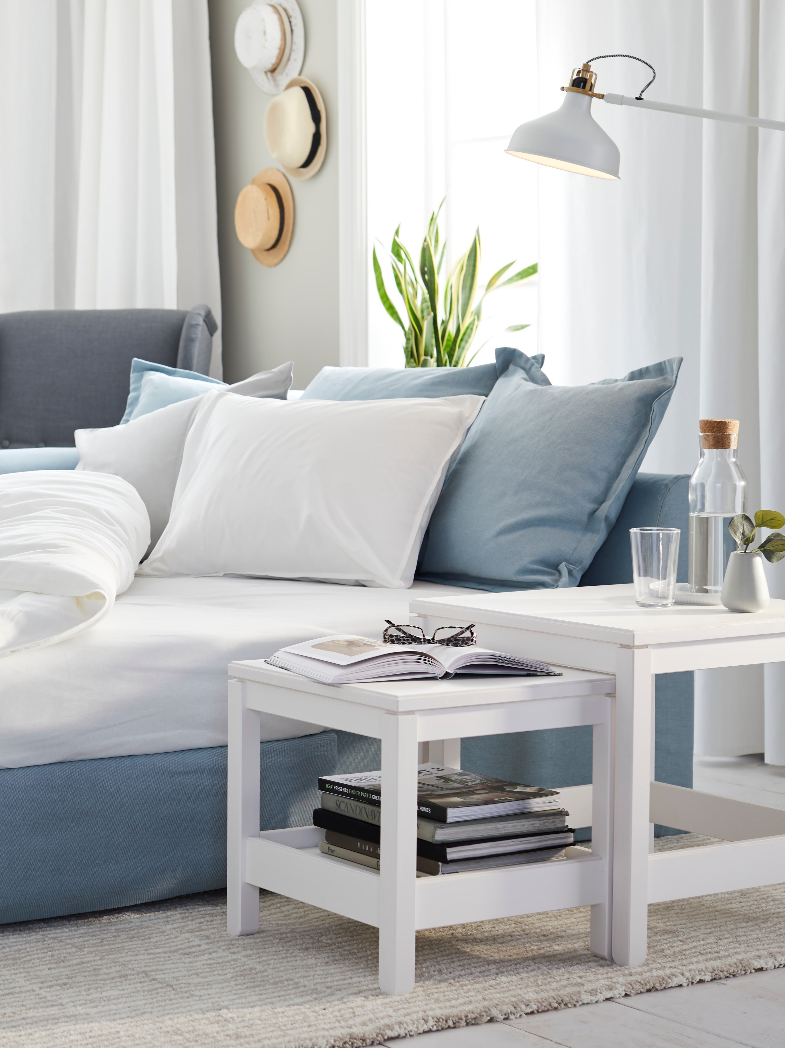 A bright living room with a light blue HOLMSUND sofa-bed set up as a bed, near side tables with books and a glass of water.