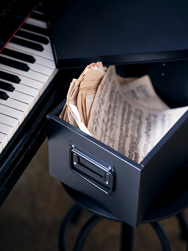 A black MANICK box with lid, containing sheets of paper with music written on them, sits on a stool beside a piano.