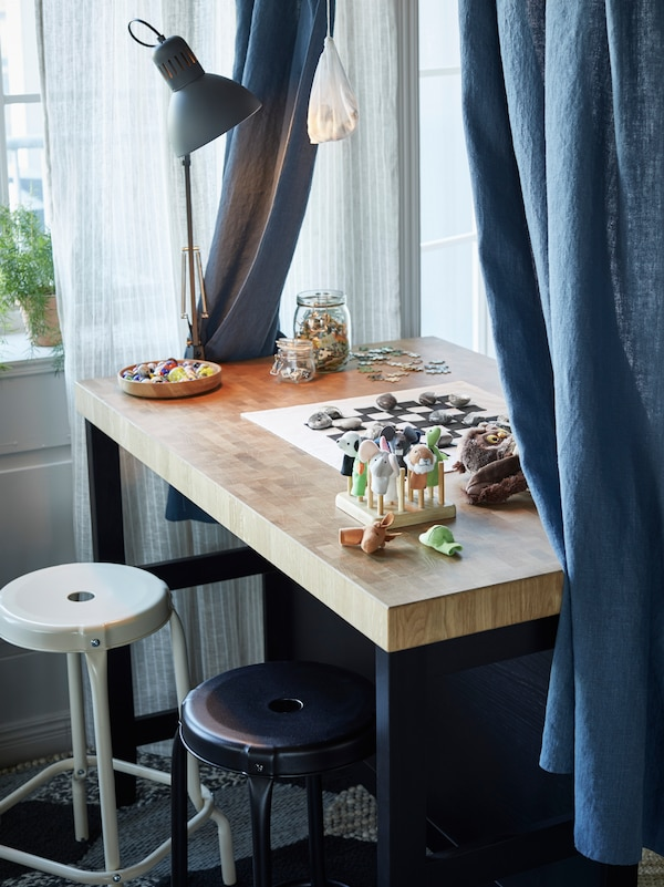 An island used as a desk with a blue/grey work lamp, blue curtains and a board game on top. Two stools are in front.