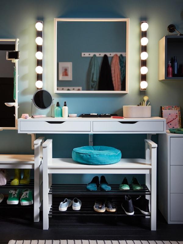 Une étagère avec tiroirs blanche EXBY ALEX sur laquelle se trouvent des articles, un miroir fixé par-dessus et des appliques de chaque côté.