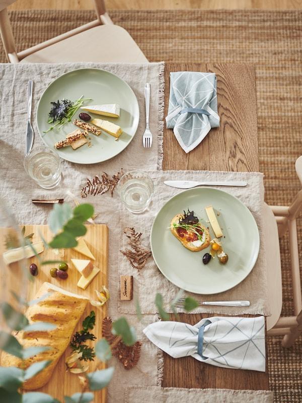 Mesa inspiradora com pratos FÄRGKLAR em mate verde, individuais feitos com tecido AINA, faqueiro MOPSIG. Tábua de cortar em bambu.