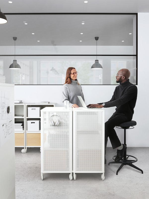 A man and a woman in an office talking to each other beside a white storage unit. Lamps hang from the ceiling behind them.