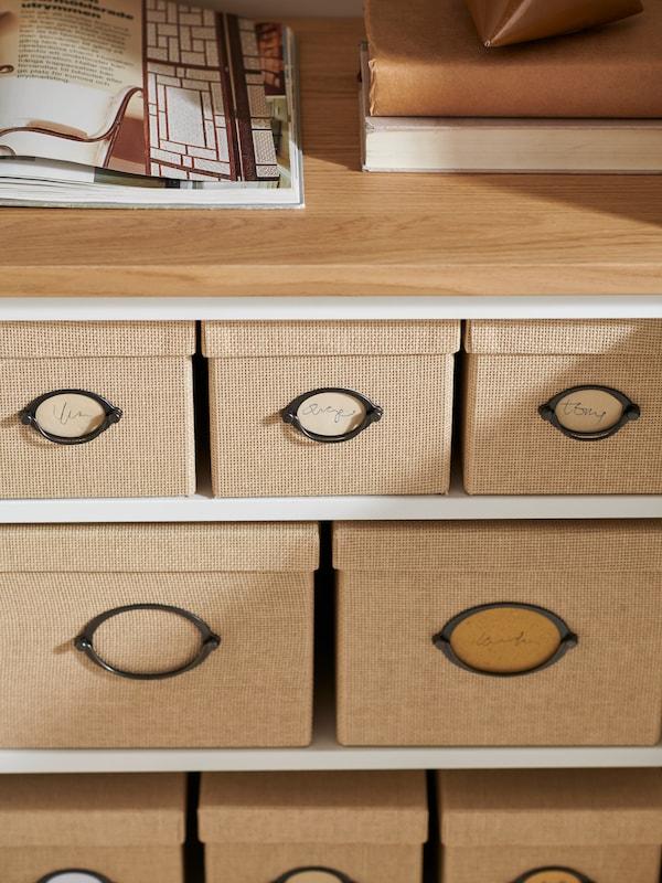 Des étagères BESTÅ avec des livres et un magazine posés dessus, et plusieurs boîtes KVARNVIK beiges avec couvercles, de différentes tailles, rangées à l'intérieur.