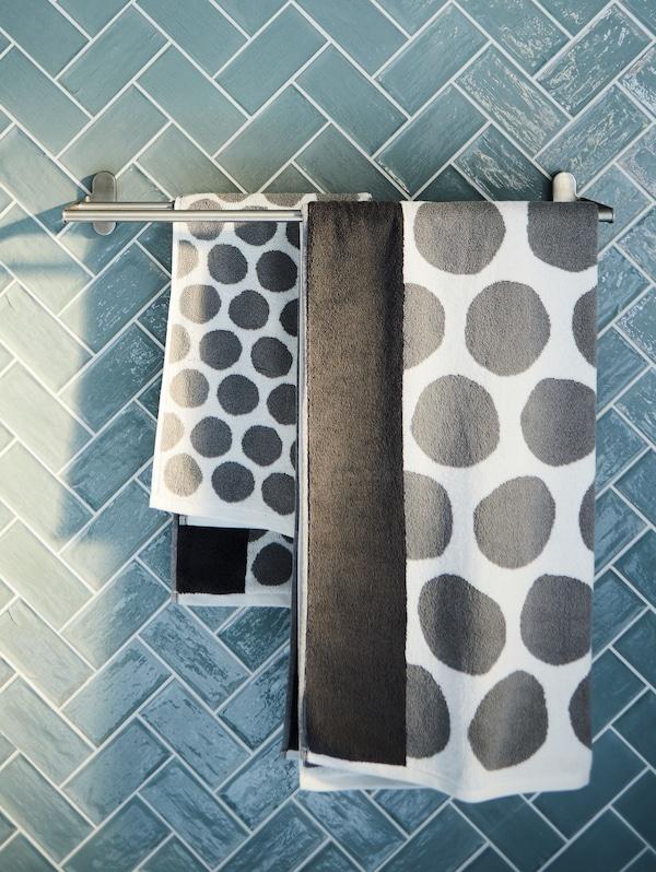 Білі та антрацитові рушники з малюнком висять на штанзі для рушників з нержавіючої сталі на фоні сірої/синьої кахельної стіни.