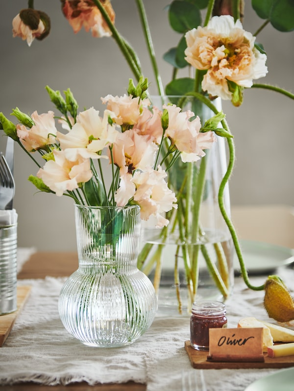 A section of a festively set table with colourful flowers placed in side-by-side PÅDRAG and BERÄKNA clear-glass vases.
