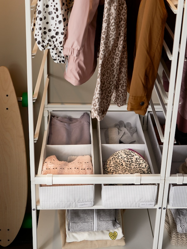 STUK boxes with compartments containing clothes sit on a shelf in JONAXEL storage underneath some hanging clothes.