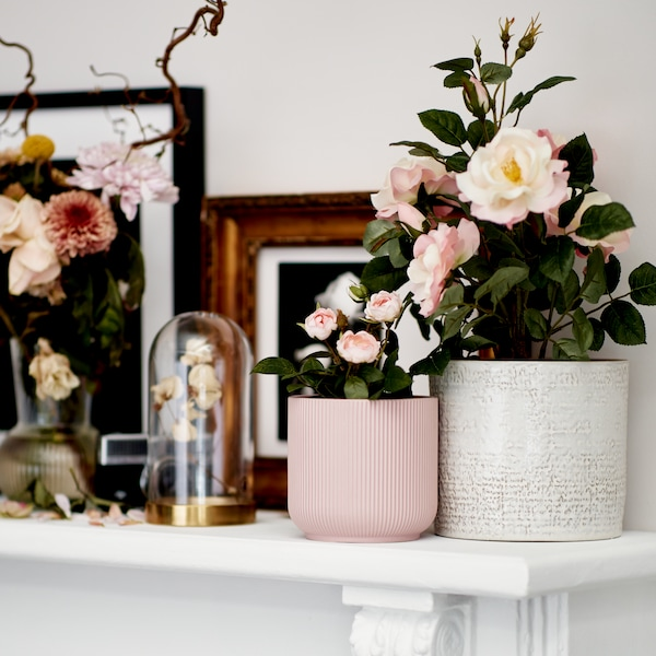 A white mantelpiece decorated with pink and white flower pots, a vase, and a bell jar holding artificial flowers.