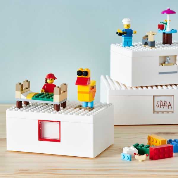 BYGGLEK LEGO® boxes with lids and toy bricks sit on a floor with toy figures and toy furniture built from the bricks.