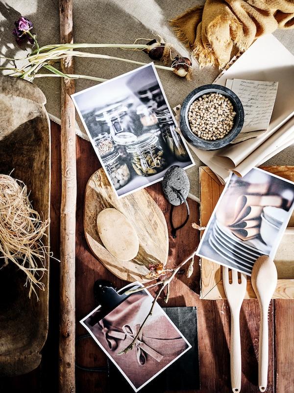 Une table en bois rustique sur laquelle se trouvent des fleurs séchées, des photos, de la paille, du tissu, une cuillère en bois, une fourchette et une planche à découper.