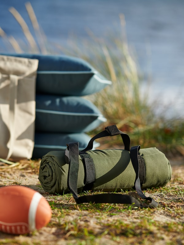 A green, rolled-up FJÄLLMOTT picnic blanket with carrying straps, lying on a beach beside stacked cushions and a toy ball.