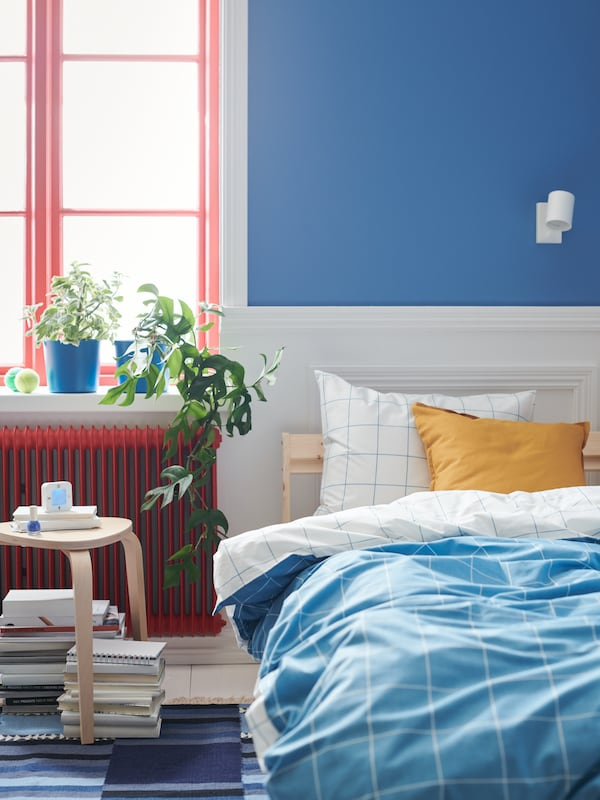 Book stacks and a KLOCKIS alarm clock by a bed with blue-and-white, chequered VITKLÖVER bed linen. Plants in the window.
