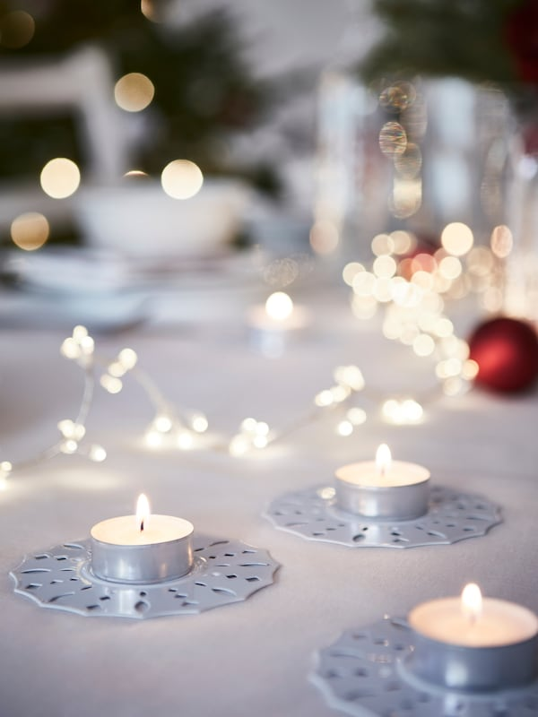 GLIMMA unscented tealights on a table with lights and flowers.