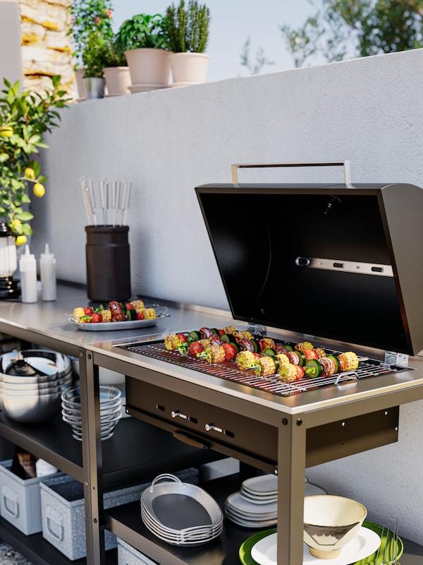 Ein Holzkohlegrill mit offener Haube. Auf dem Grill sind Gemüsespiesse zu sehen, auf der Fläche darunter Teller und Tabletts.