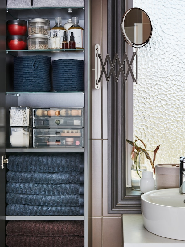 Open bathroom cabinet with blue towels folded on shelf. Other organizational items stacked on shelves