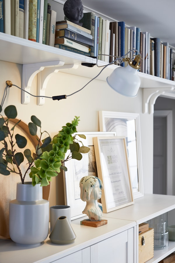 A room featuring a side table featuring vases, picture frames and a bookshelf.