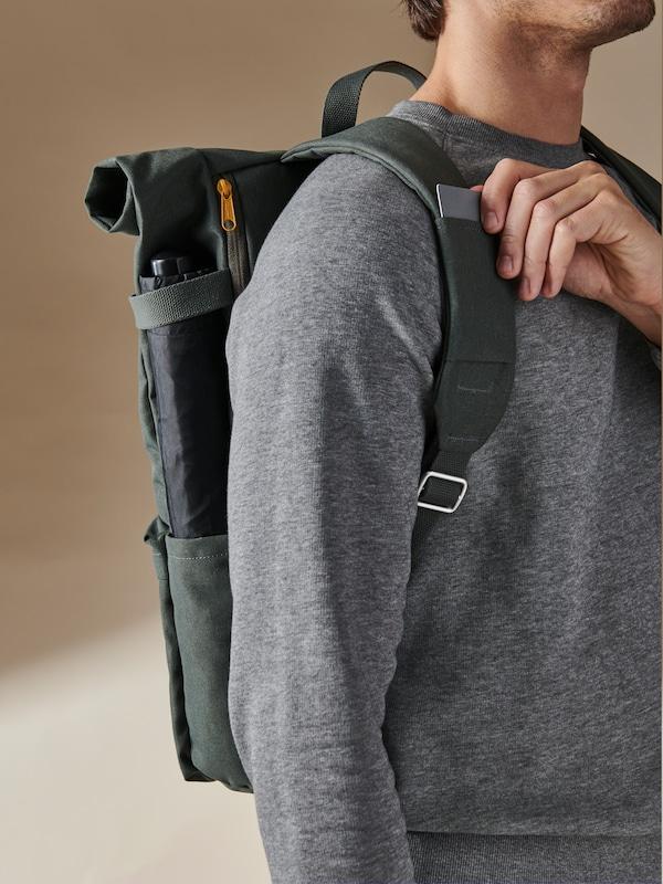 Un homme portant un sac à dos DRÖMSÄCK vert sort une carte de la fente située sur l'une des bandoulières.