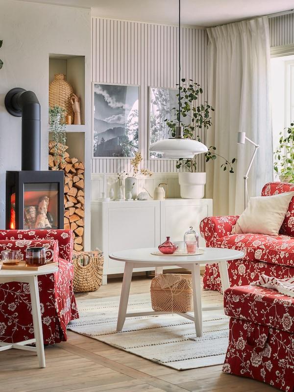 Ein rot und weiß gemustertes Sofa mit Kissen in verschiedenen Farben, einem passenden Hocker und dahinter Pflanzen und Fenster.