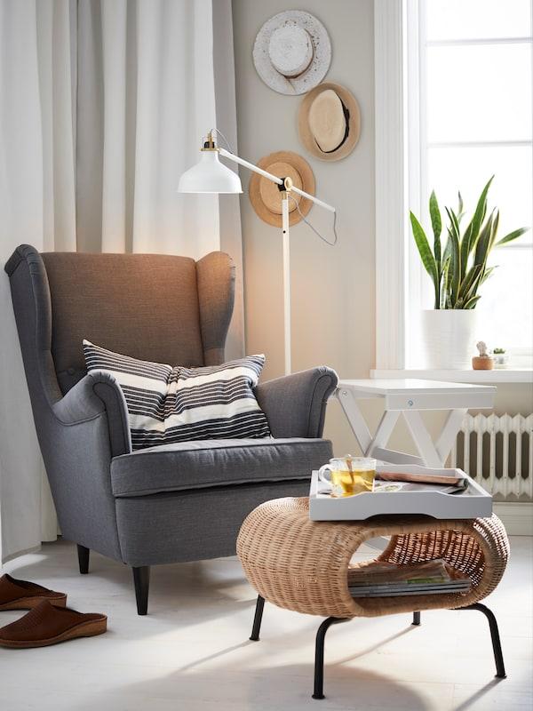En grå STRANDMON lænestol og en fodskammel i naturflet.