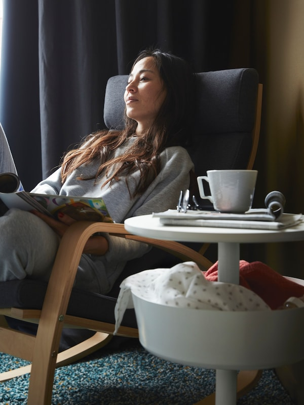 A woman relaxing in an armchair, with a side table holding a coffee cup, a plate and diverse items.