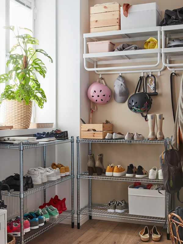 Two metal OMAR shelving units with shoes and boots stand in a corner next to a window, near two MACKAPÄR hat and coat racks.