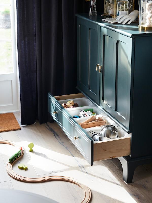 Een groene kast met open lade met speelgoed naast een open groene gordijn en een houten treintje.