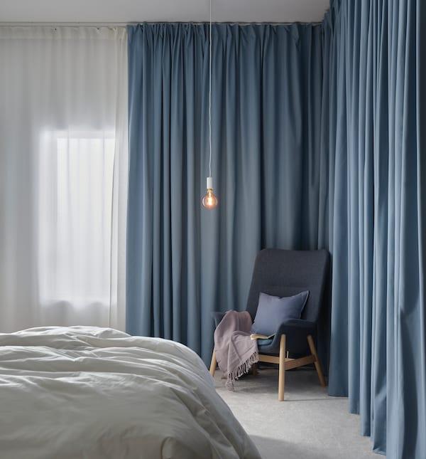 Ett sovrum med blå gardiner och en blå fåtölj.