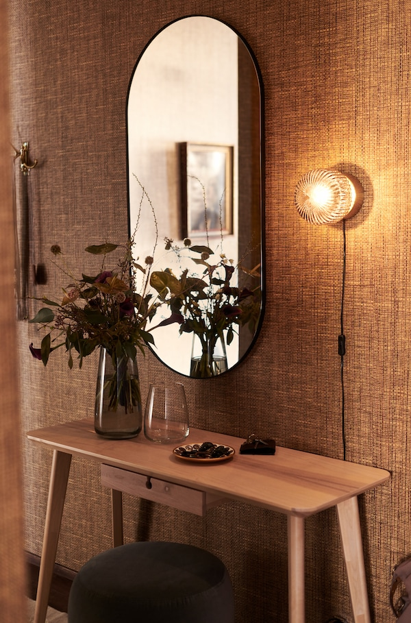 bureau avec un vase et un bouquer de fleur posé dessus, un miroir oval fixé au mur