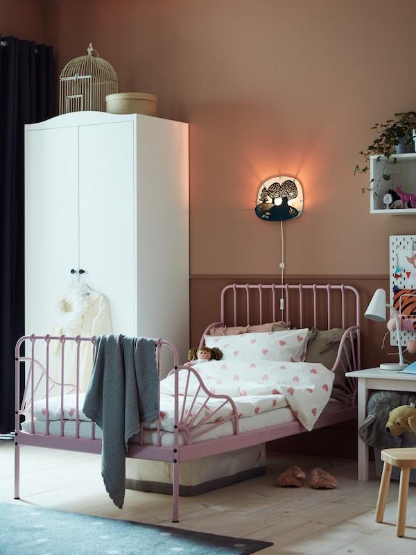 En lyserød udtræksseng med lamelbund og en mørk turkis/lys turkis LED-væglampe med skovtema.