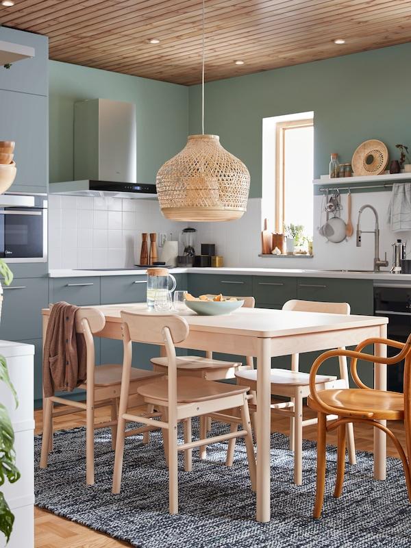 Mesa RÖNNINGE y sillas de abedul sobre una alfombra tejida a mano, con una lámpara de techo de bambú sobre ella, en una cocina con frontales grises.