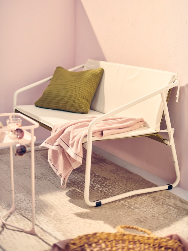 A white INGMARSÖ outdoor sofa with a green cushion and pink towel on a sunny urban balcony with light pink walls.