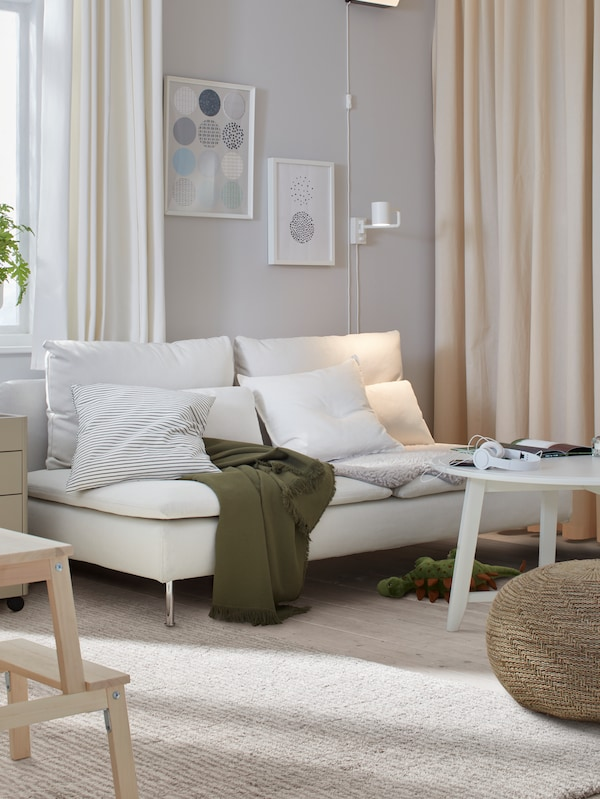 A white sofa with cushions and a green throw, a coffee table, pictures in picture frames on the wall, and curtains.
