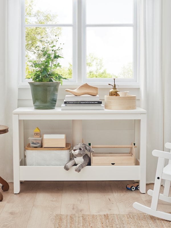 A HAVSTA console table with decorative objects on the top and children's toys on the high-edged storage shelf beneath.