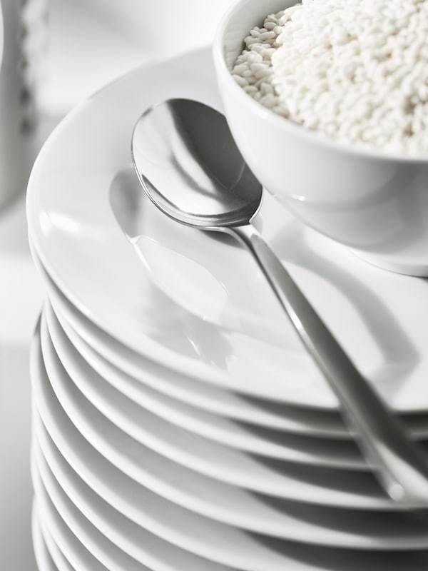 A pile of white plates that has a white bowl filled with cereal on top, with a FÖRTNUFT spoon beside it.