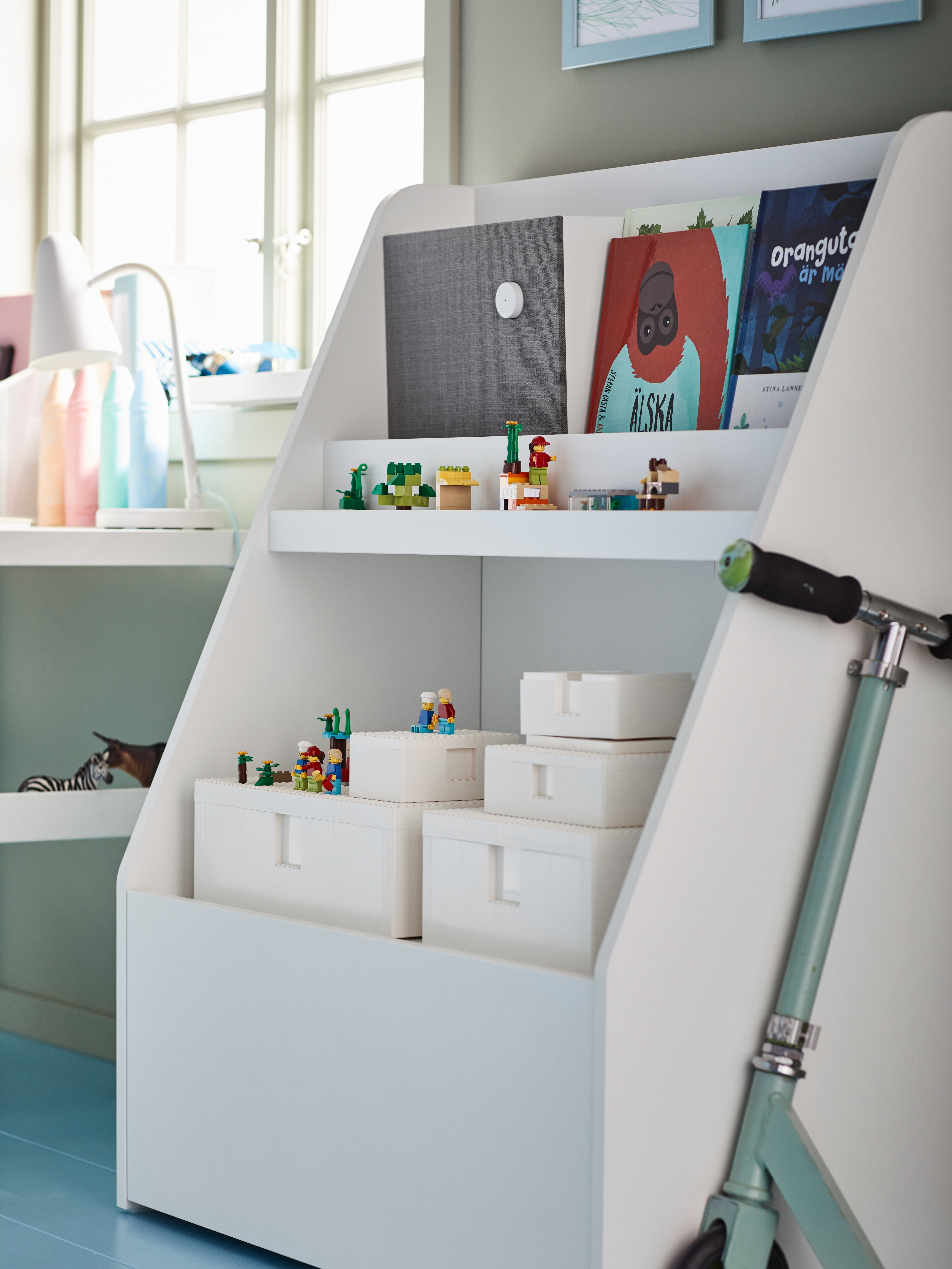 A book display holding books, a Bluetooth® speaker and several white BYGGLEK LEGO® boxes with lids and building blocks.
