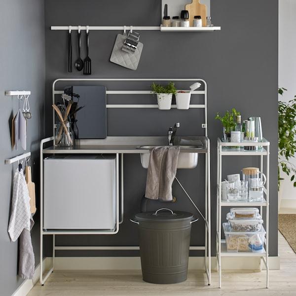 Eine SUNNERSTA Mini-Küche vor einer dunkelgrauen Wand und ein Servierwagen mit Gläsern, Kunststoffbehältern und Dosen mit Deckeln.