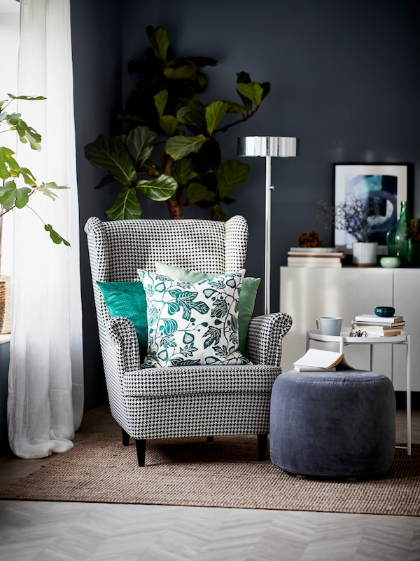 A room with a gray armchair with green and white cushions, blue ottoman, a standing floor lamp and white storage.