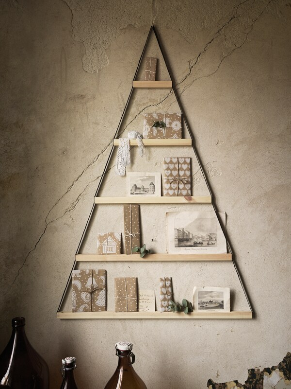 Display unit on a wall in the form of a triangle, with the shelves holding various sized presents in wrapping paper.