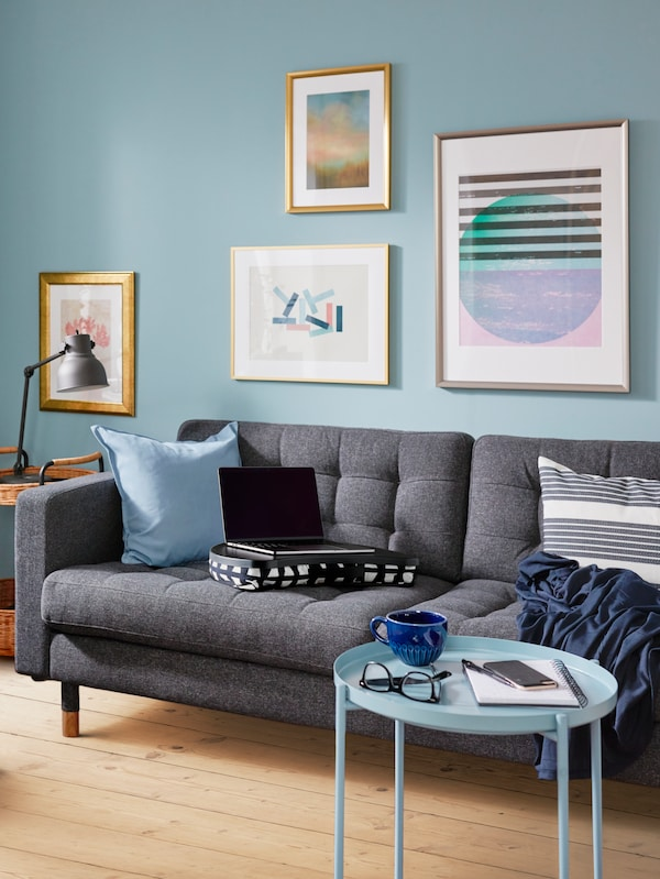 A gray sofa with assorted cushions on it, a coffee table, and a blue wall behind with pictures in frames on it.