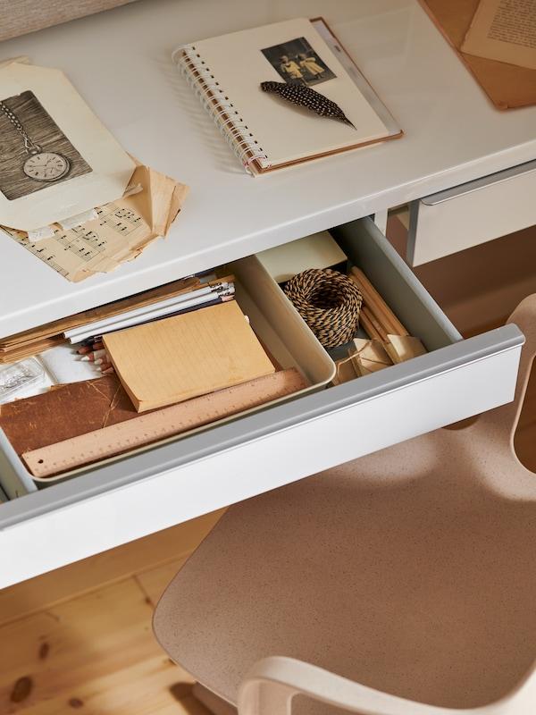 Un bureau avec un cahier posé dessus et un range-tout NOJIG en plastique beige pour bien ranger la papeterie dans le tiroir.