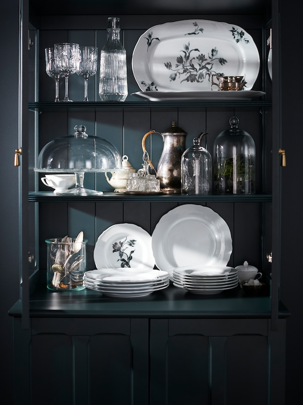 A dark cabinet filled with glassware, white dishes and dramatic decor.