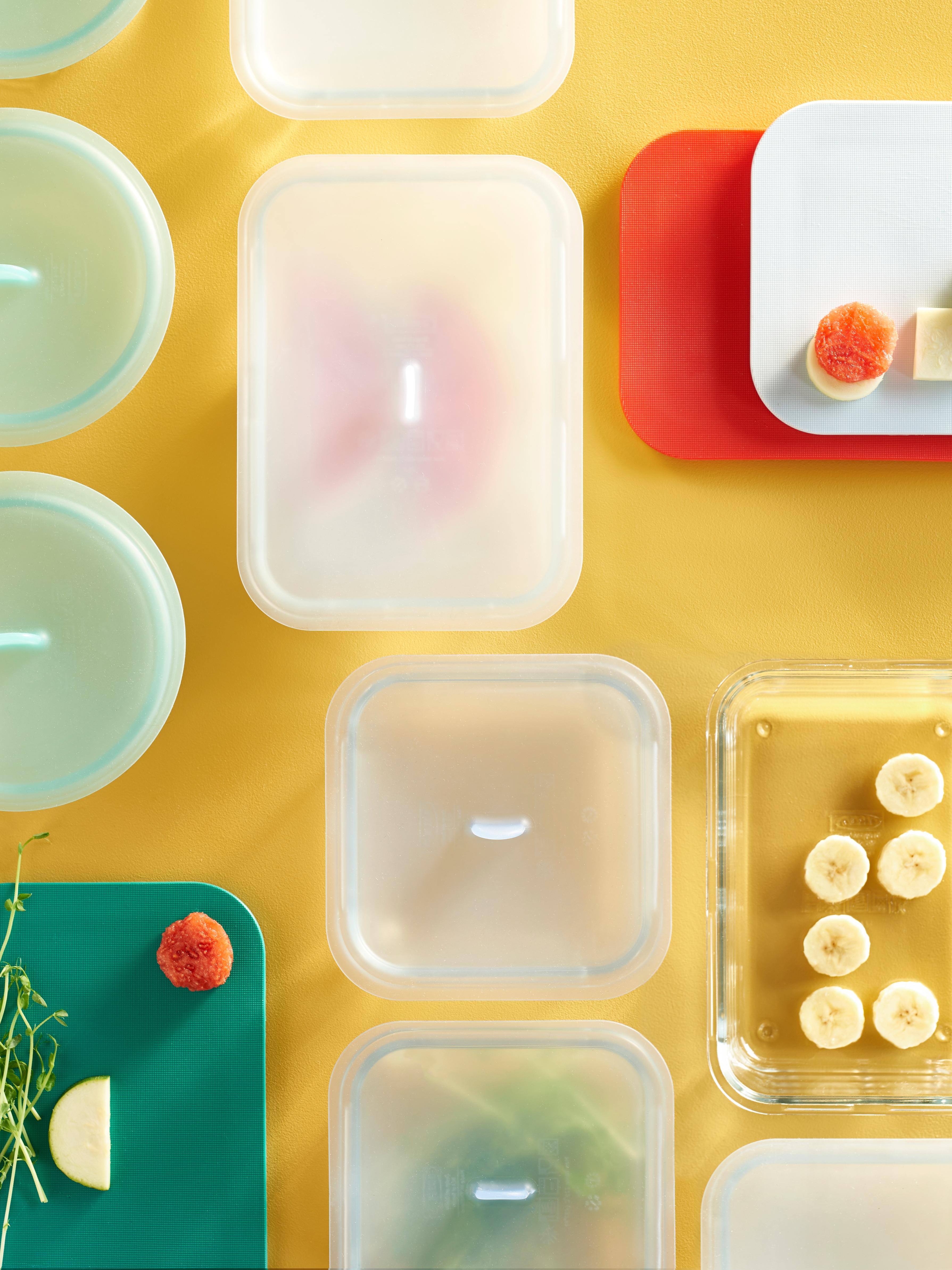 Niz IKEA 365+ posuda za hranu, neke s poklopcima, raspoređenih na žutoj radnoj ploči.