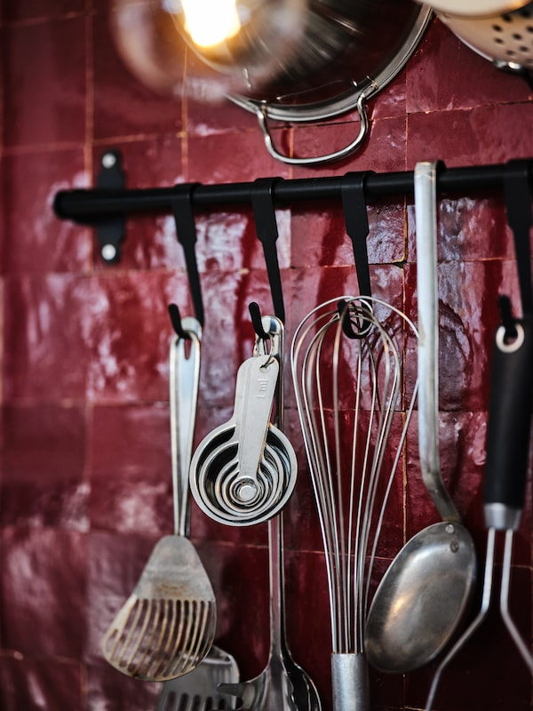Close up of dark kitchen setting with glossy, dark red brick wall. Black HULTARP rail system on wall with several small measuring spoon hanging from hook