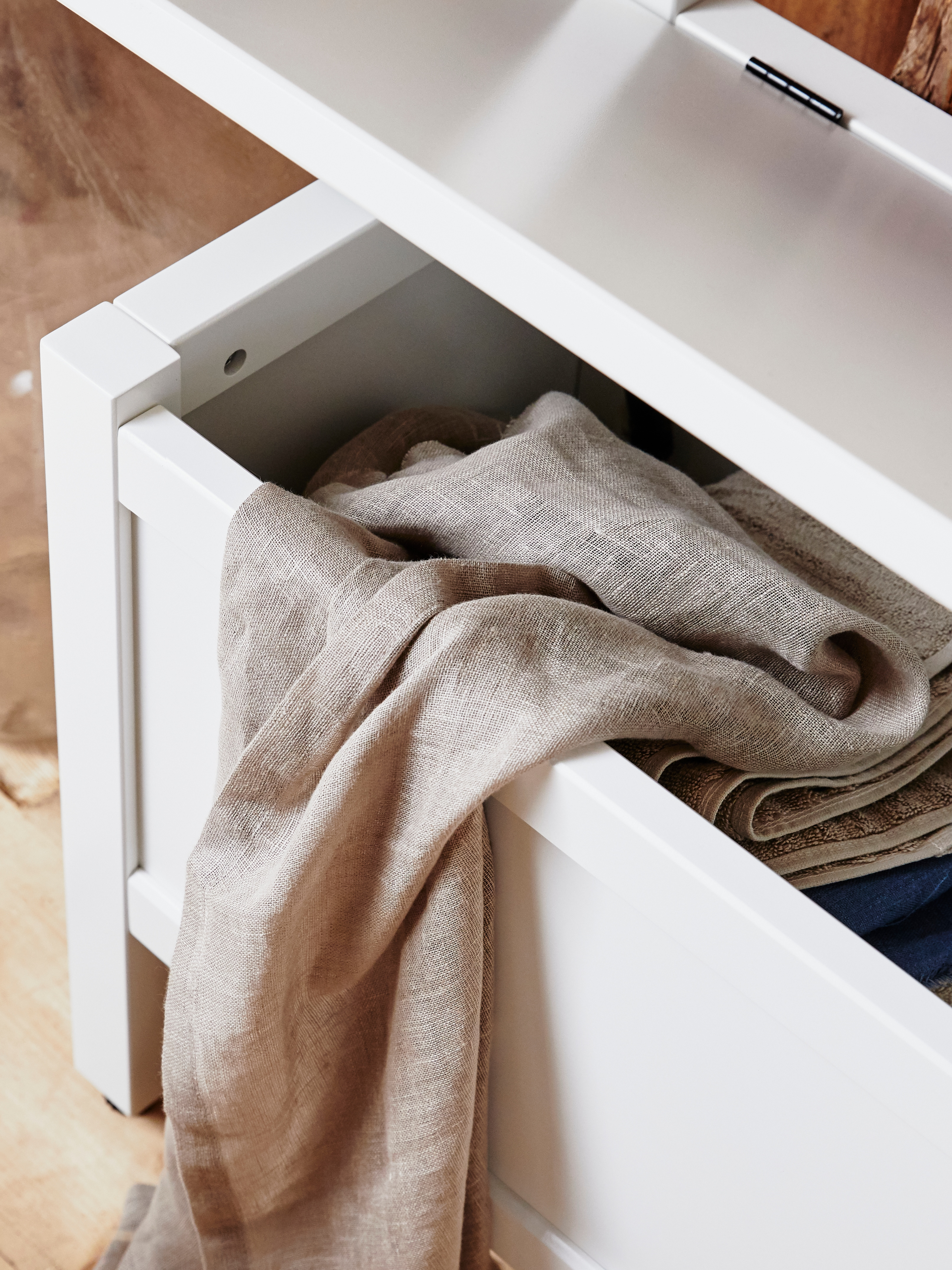 A close-up shows a lifted, hinged top, and beige towels inside a white HEMNES storage bench, with towel rail.