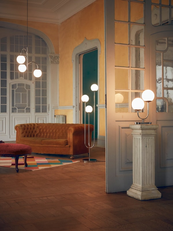A grand room with a pendant, floor and table lamp from the SIMRISHAMN collection. A classic sofa is in the background.