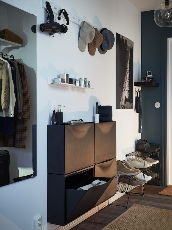 Black shoe cabinets on the wall, a narrow shelf with small boxes, two white racks with knobs with caps and headphones.